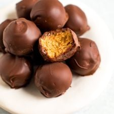 Plate of healthy peanut butter balls covered in chocolate. One has bite taken out of it.