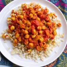 Channa Masala served with brown rice on white plate and colorful placemat.