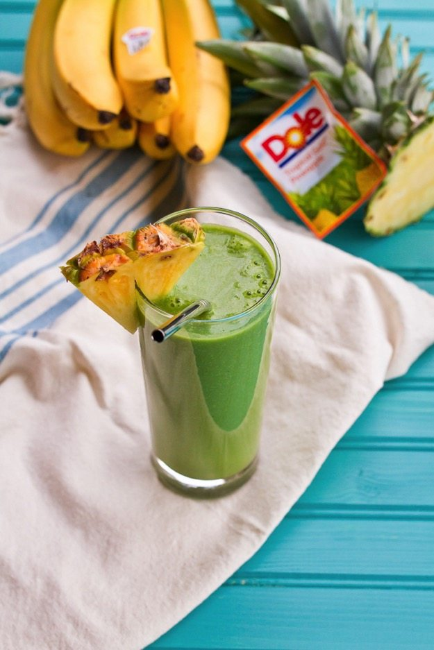 Vitamin C Booster Green Smoothie served in a tall clear class with slice of pineapple, bunch of bananas in background.