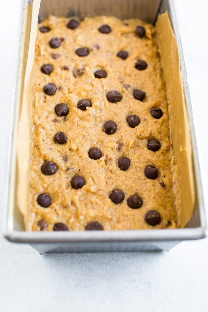 Unbaked batter for chocolate chip coconut flour banana bread in a loaf pan topped with extra chocolate chips.