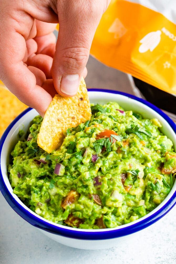 Hand dipping a chip into a bowl of frozen pea guacamole.