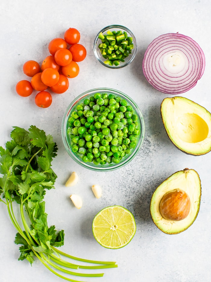 Ingredients for pea guacamole on a table: tomatoes, jalapeño, red onion, avocado, lime, garlic, cilantro and a bowl of frozen peas.