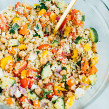 Quinoa chickpea salad in a large clear glass bowl with a gold spoon.