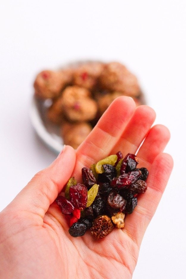 Superfood berries in the palm of a hand with superfood energy balls in the background.
