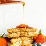 Pyrex measuring cup pouring maple syrup over two slices of stuffed french toast on a plate with berries.