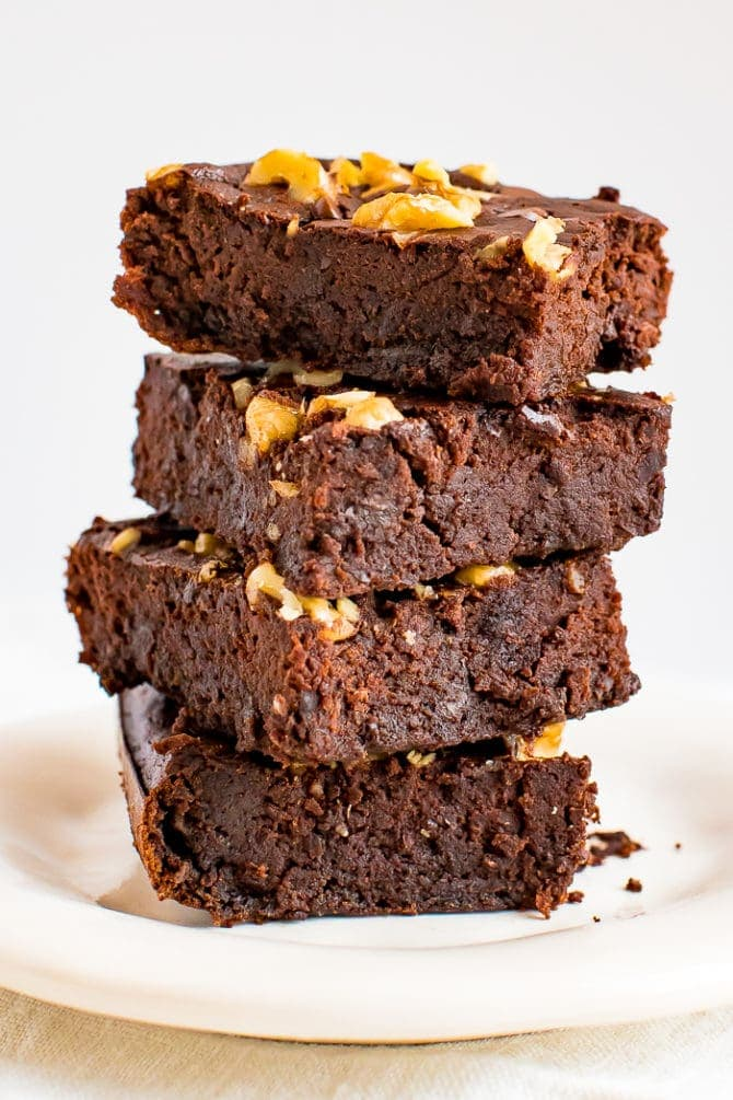 Stack of flourless back bean brownies, topped with chocolate chips and walnuts.