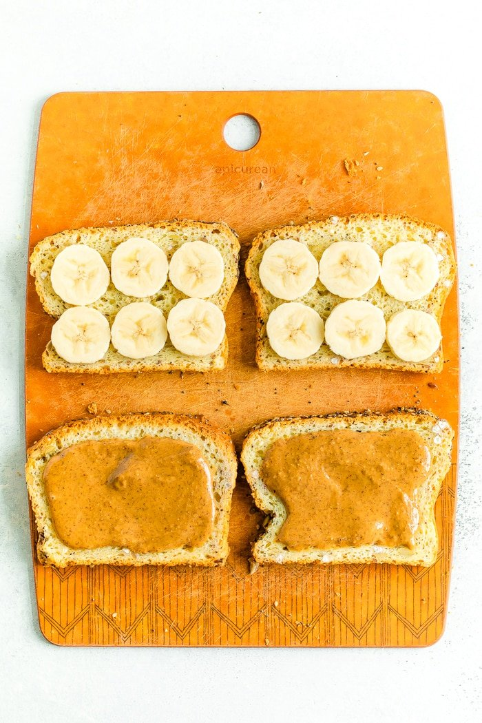 Cutting board with two slices of bread with banana slices, and two slices with almond butter.
