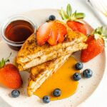 Banana and almond butter stuffed french toast on a plate with berries and topped with maple syrup.