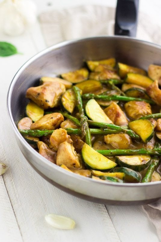 Honey Mustard Chicken Stir Fry in a silver pan on white wood counter