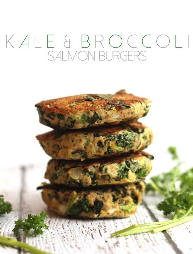 Kale and Broccoli Salmon Burgers stacked on a white table.