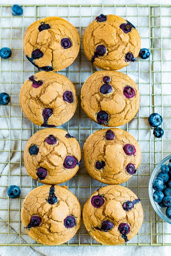 Eight blueberry muffins on a cooling rack surrounded by blueberries.