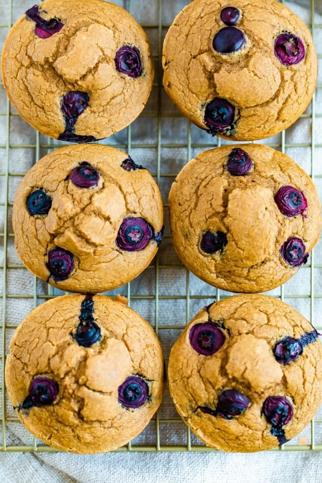 Six blueberry muffins on a cooling rack.