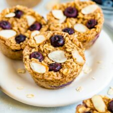Plate with blueberry baked oatmeal cups and oatmeal cups, blueberries, a bowl of blueberries and almond slivers are around on the table.