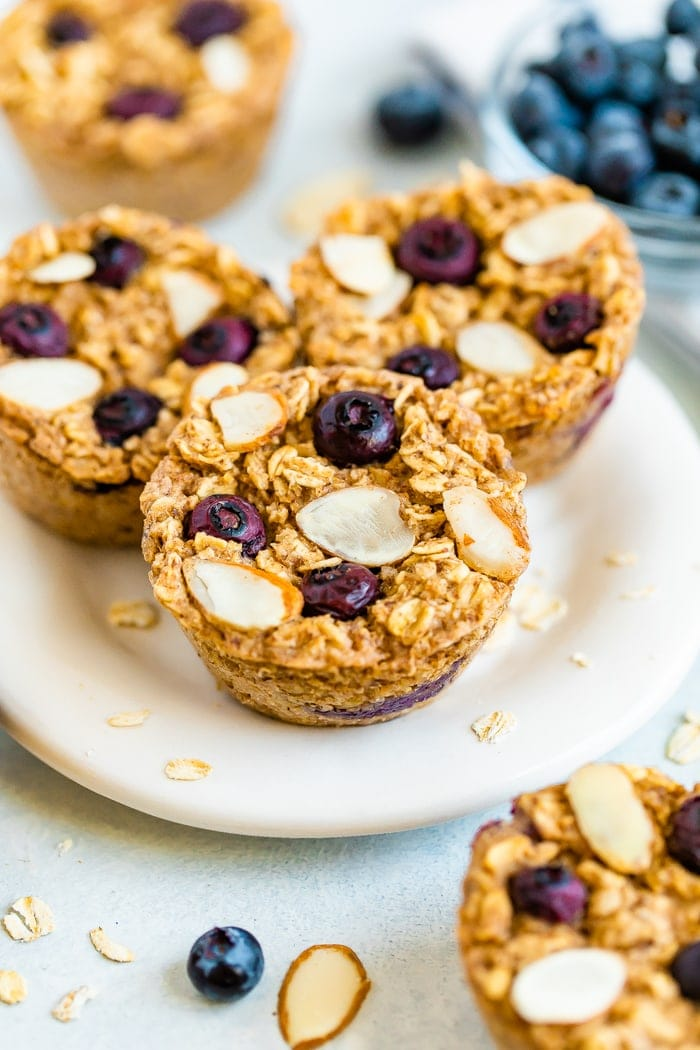 Three almond blueberry baked oatmeal cups on a plate.