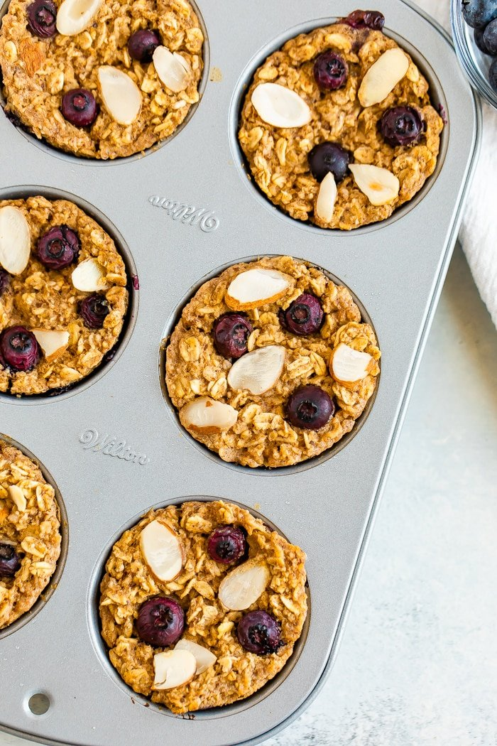 Muffin tin with blueberry baked oatmeal cups topped with almonds and blueberries.