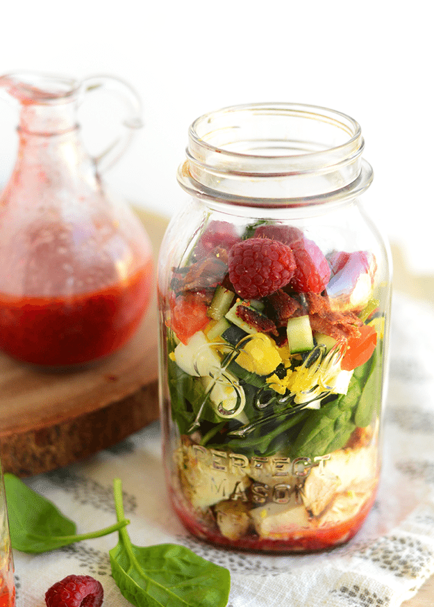 Mason jar filled with salad ingredients sitting on a kitchen towel. Red dressing in a jar sitting behind.