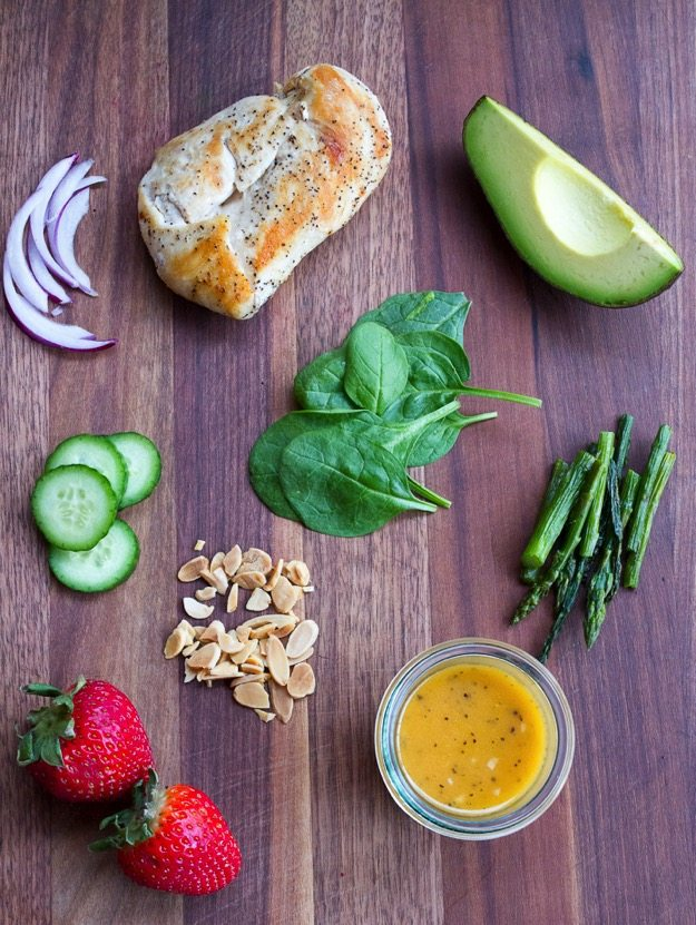 Sliced red onions, sliced cucumbers, two whole strawberries, full spinach leaves, slivered almonds, chopped asparagus, quarter of an avocado, one chicken breast, and small jar of dressing sitting on a wood cutting board.