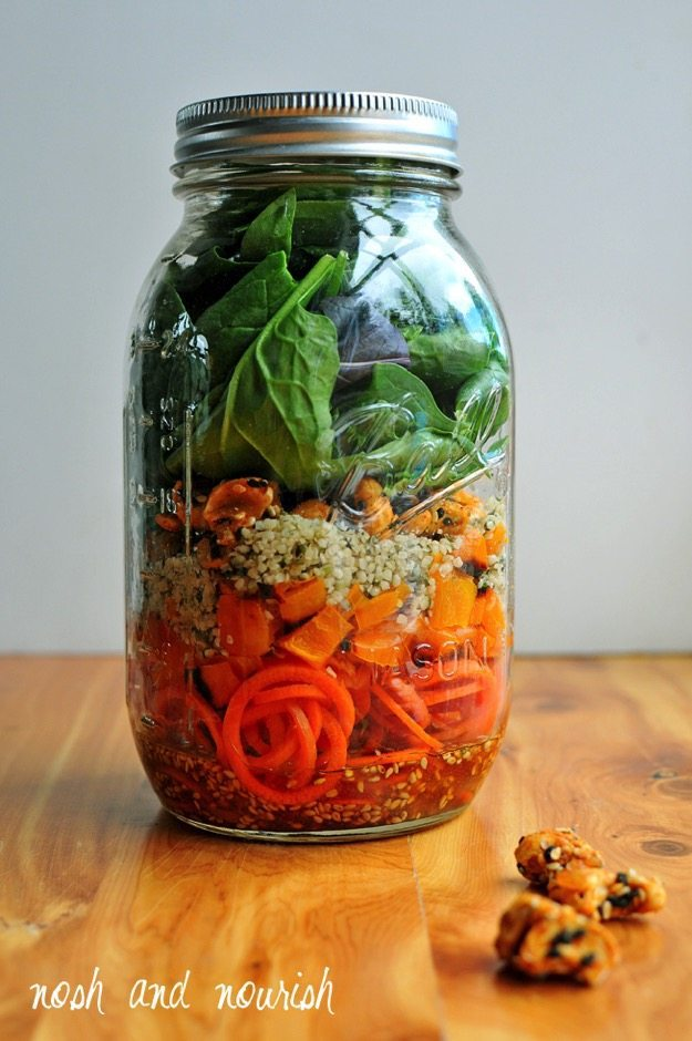 Mason jar filled with salad ingredients sitting on a wood table.