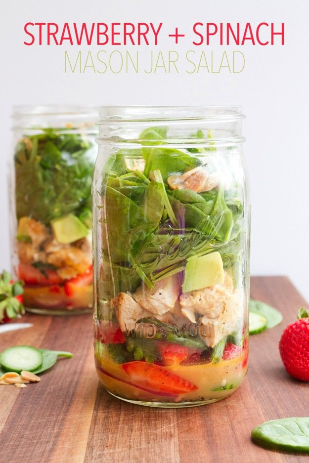 Two mason jars filled with chopped ingredients for a salad sitting on a wood cutting board.