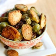 Date sweetened balsamic glazed brussels sprouts in a decorative serving bowl.
