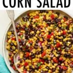 Serving bowl with black bean and corn salad. Spoon is in the bowl.