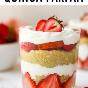 Strawberry, yogurt and quinoa parfaits, layered in a two glasses. A bowl of strawberries is behind the two parfaits.