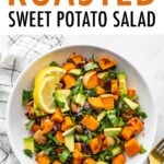 Bowl of roasted sweet potato salad with cranberries, onion, spinach and avocado.
