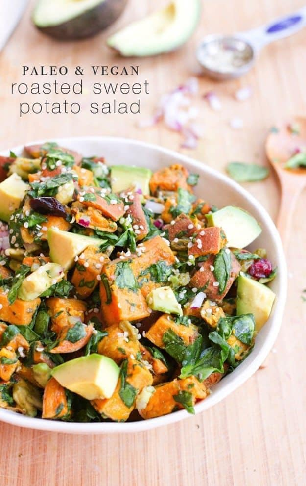 White bowl with sweet potato salad (sweet potatoes, greens, and avocado) on a wood table.