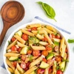 Bowl of clean eating penne pasta salad mixed with basil, cherry tomatoes, cucumber and red onion. Next to the bowl are fresh basil leaves and a wooden mixing spoon.