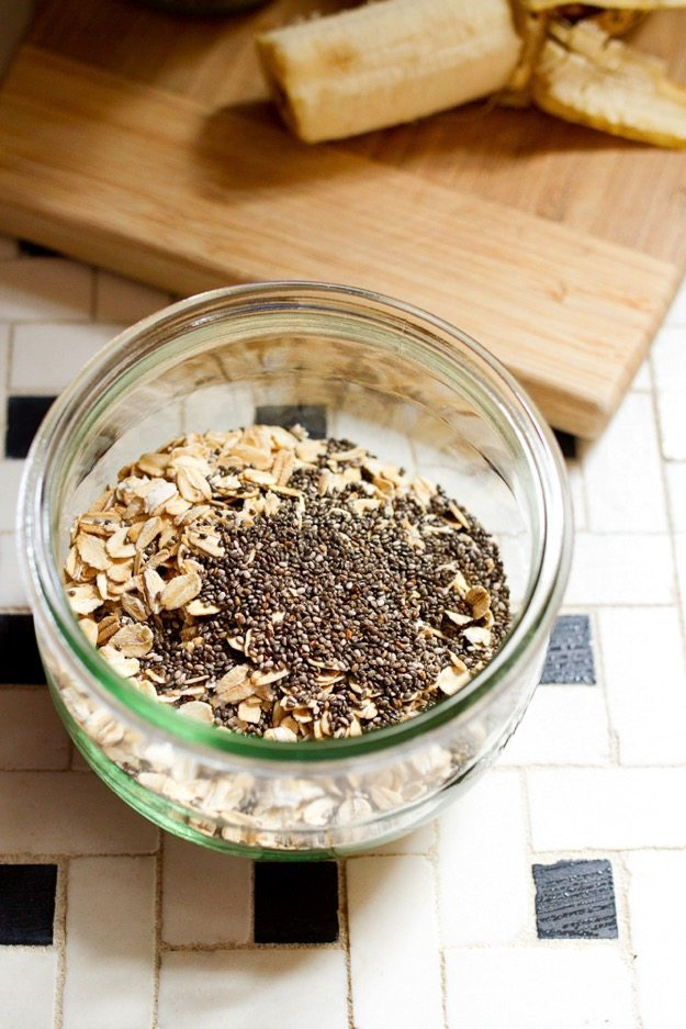 Clear jar of dry oats and chia seeds on a black and white checkered countertop. Wood cutting board with banana in background.