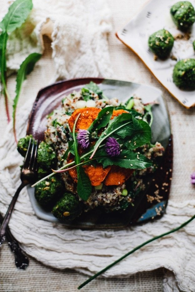 Dandelion green quinoa risotto is piled on a plate. It sits on a brown cloth.