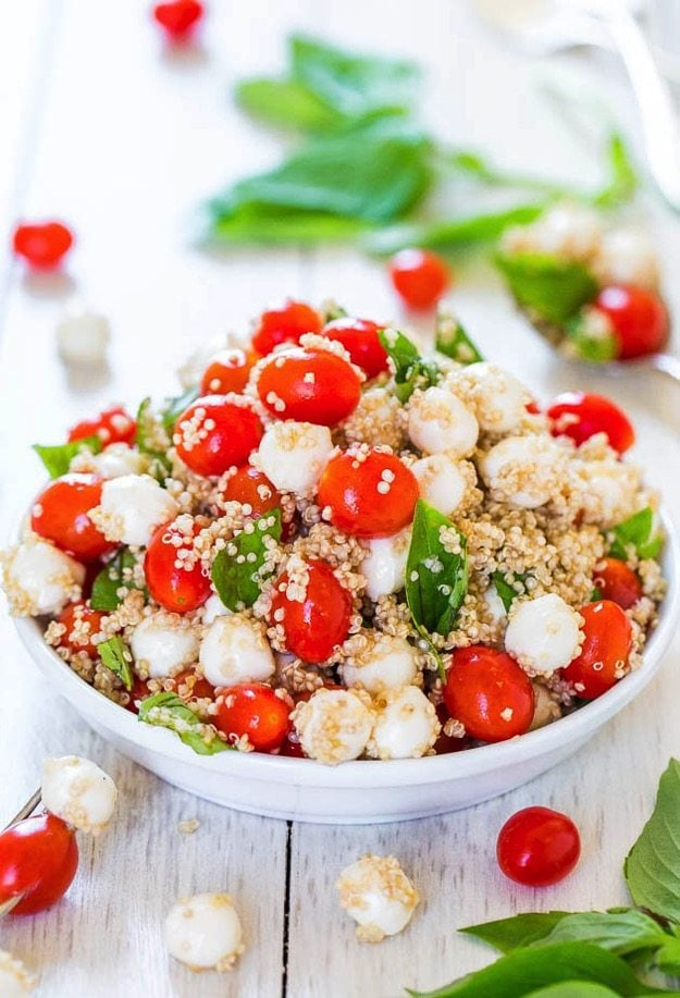 Tomato, quinoa, basil and mozzarella fill a white bowl. Basil and tomatoes surround the bowl.