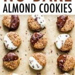 Cookie sheet lined with parchment paper. 9 no bake almond cookies half dipped in dark chocolate or white chocolate and sprinkled with cacao nibs.