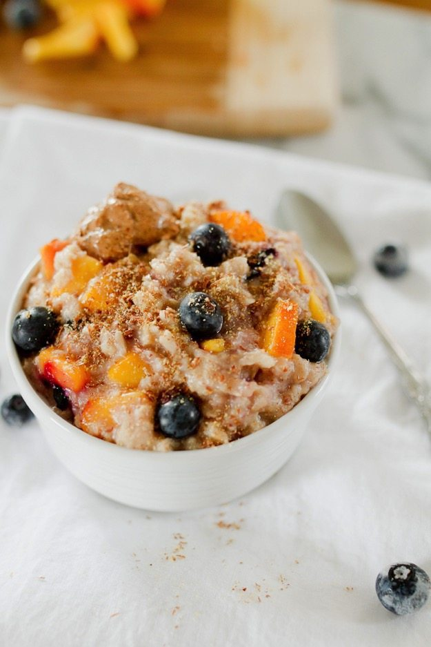 Blueberry Peach Oatmeal - Loaded with fiber, healthy fat and protein this delicious bowl of oats will keep you feeling full and energized all morning.