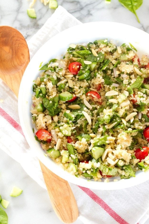 Summer Greek quinoa salad fills a white bowl. It rests on a marble countertop and a wooden spoon lays next to the bowl.