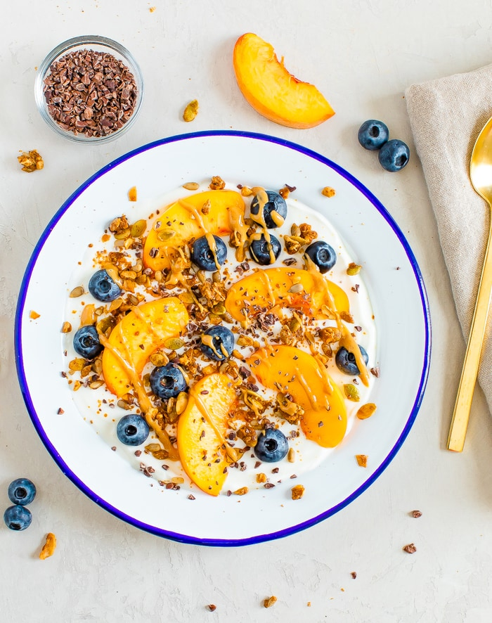 Birds eye view of Bowl of yogurt with fresh peach slices and blueberries, topped with granola, cacao nibs and nut butter. Bowl of cacao nibs, a slice of peach and a few blueberries are around the bowl.