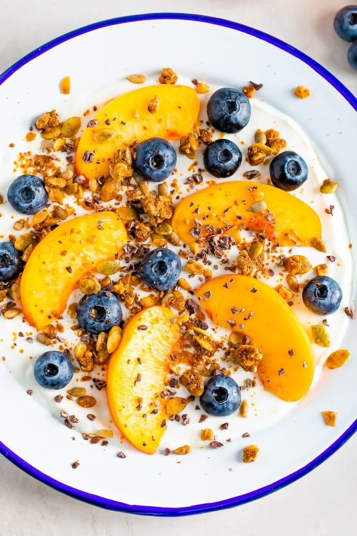 Bowl of yogurt with fresh peach slices and blueberries, topped with granola, cacao nibs and nut butter.