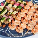 Grilled skewers of shrimp and zucchini, onion, and mushrooms on a navy serving tray.