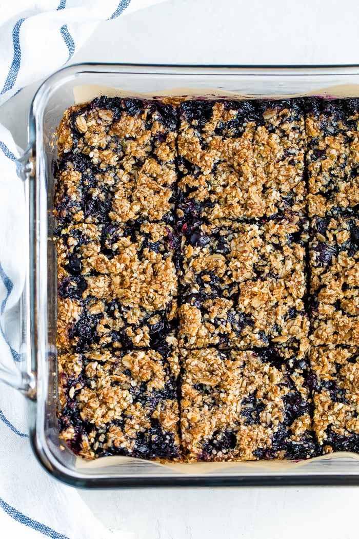 A square glass baking dish with blueberry crumble bars cut into 9 squares. A dish cloth is around the dish.
