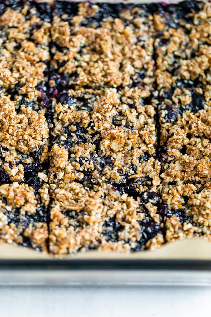 Close up of blueberry crumble bars sliced in a pan. The bars are topped with an oat and hemp crumble.