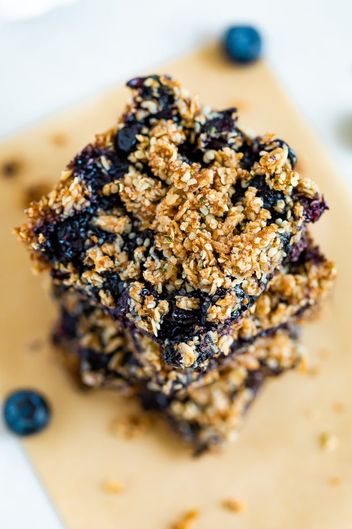 Stack of blueberry crumble bars. Close up of the top of the bar with an oat and hemp seed crumble.