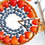 Greek yogurt tart decorated with strawberries and blueberries. A striped dish towel, sliced strawberries, and blueberries surround the tart. A slice is cut for one piece in the tart.