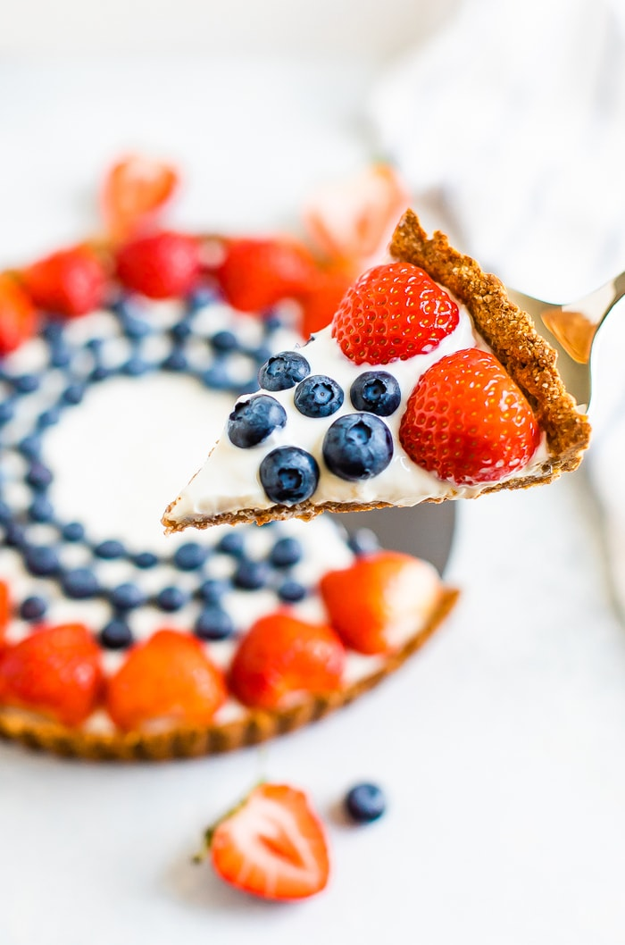 Silver pie spatula holding a slice of greek yogurt berry tart topped with strawberries and blueberries. The rest of the tart is in the background.
