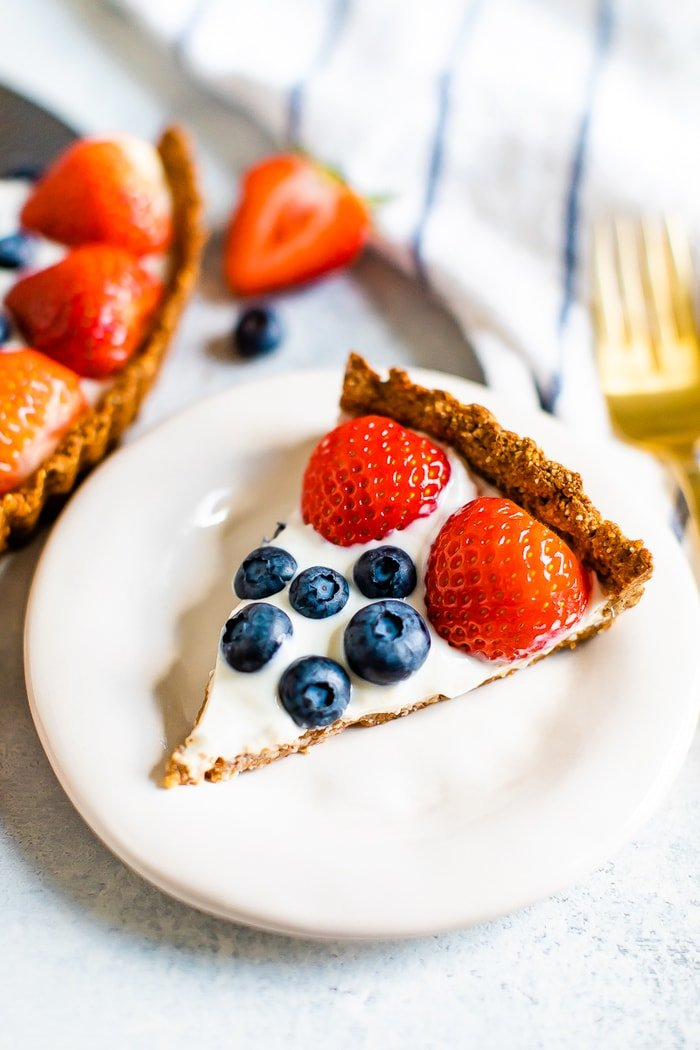 Slice of greek yogurt berry tart with strawberries and blueberries on a plate. A fork, striped napkin, and tart are beside the plate.