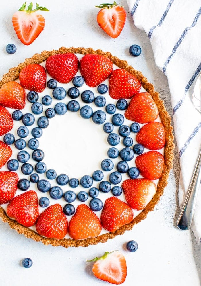 Greek yogurt tart decorated with strawberries and blueberries. A striped dish towel, sliced strawberries, and blueberries surround the tart.