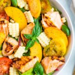 Salad topped with grilled salmon, corn, basil, peaches, and tomatoes.