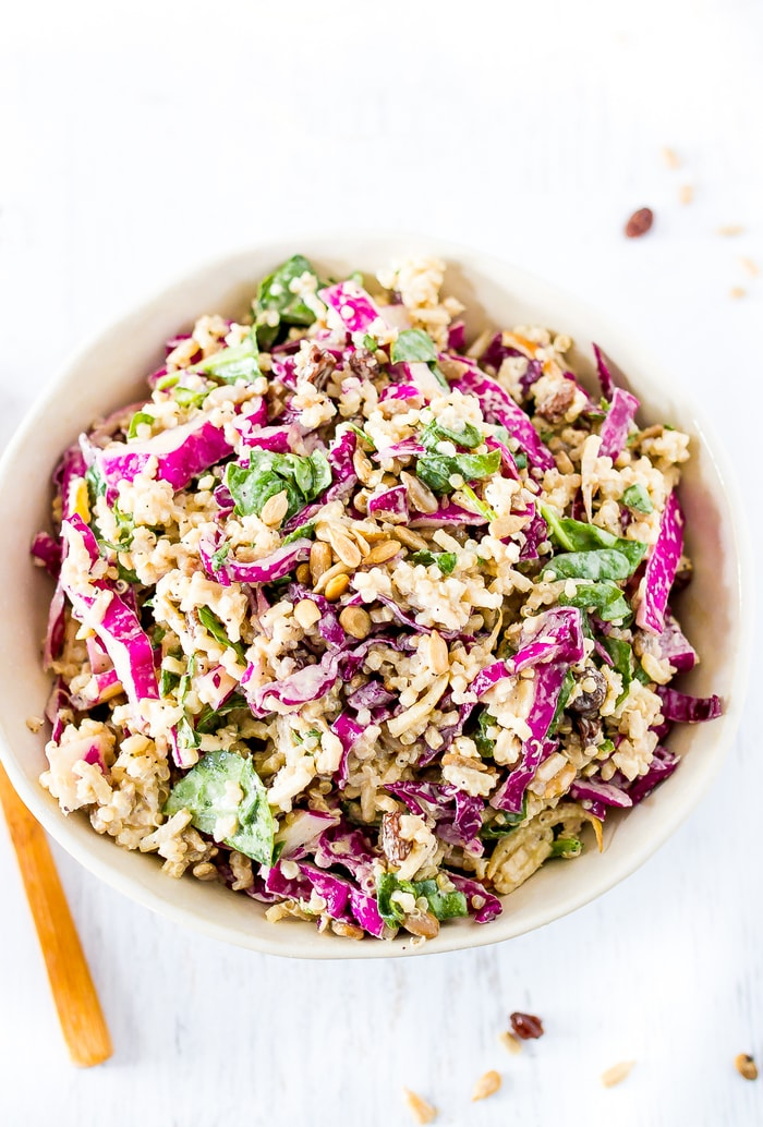 Bowl of spiralized apple slaw, filled with apples, spinach, quinoa and cabbage. The corner of the fork to the side.