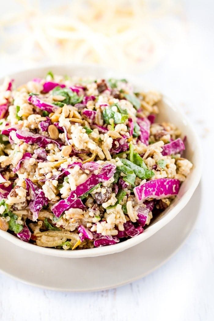 Bowl of spiralized apple slaw, filled with apples, spinach, quinoa and cabbage.