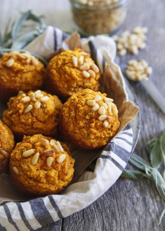Toasted pine nut herb pumpkin muffins in a bowl lined with a towel.