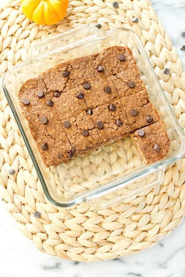 Pumpkin Protein Bars in a clear baking dish on a woven place setting.